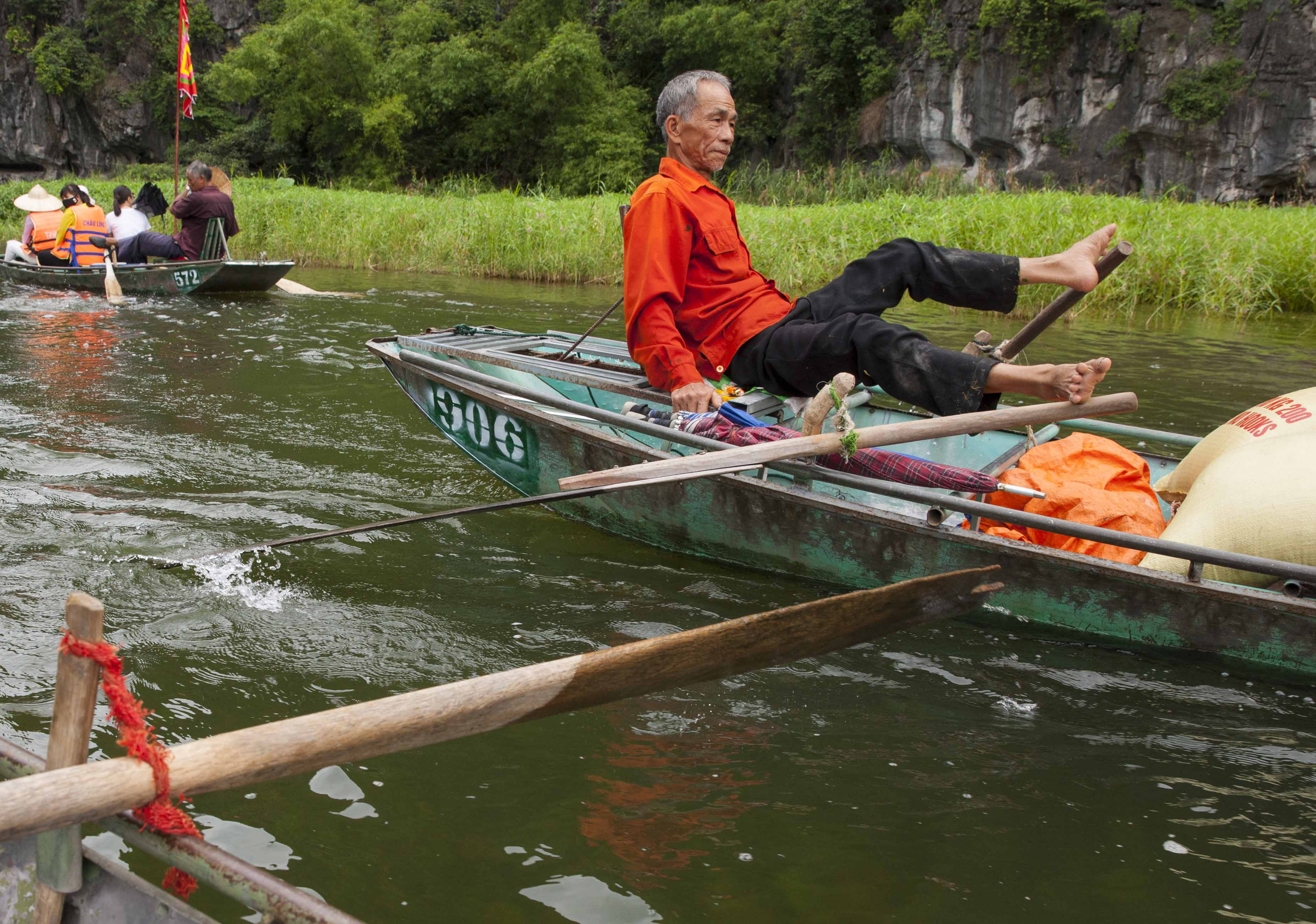 A-man-is-rowing-boat-ride-at-tam-coc - Hanoi Explore Travel